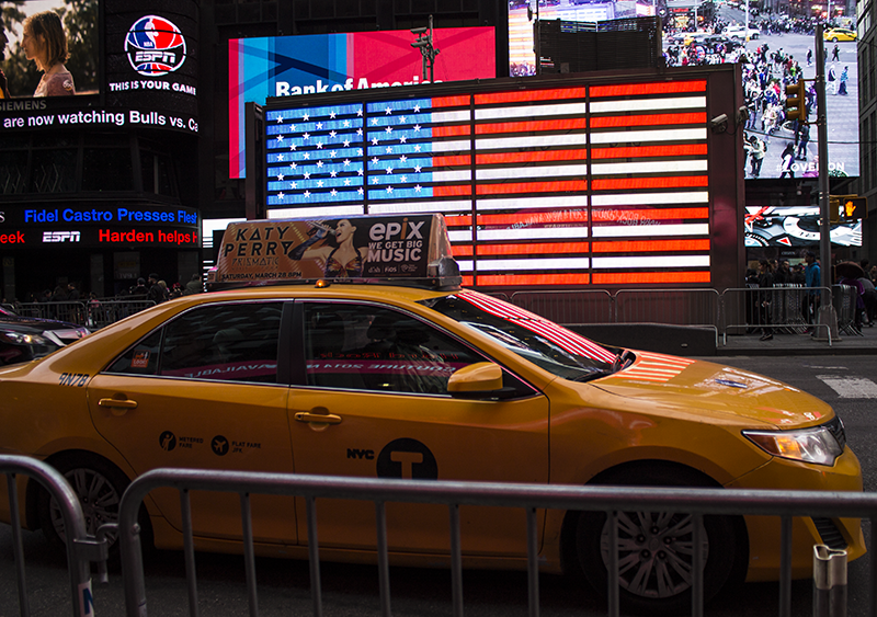 Yellow cab and USA flag Times Square New York